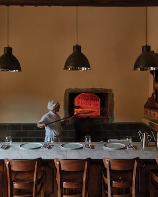 Chef next to a banquet table placing pizza on a paddle into a glowing pizza oven
