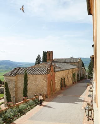 Aerial view of a rustic stone-built Tuscan chapel with an ornate facade