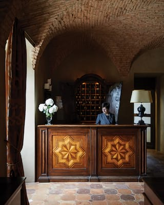 Concierge standing behind a wooden reception desk with a carved star relief