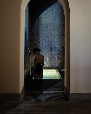 Silhouette of a lady before a glowing underlit plunge pool in an underground spa