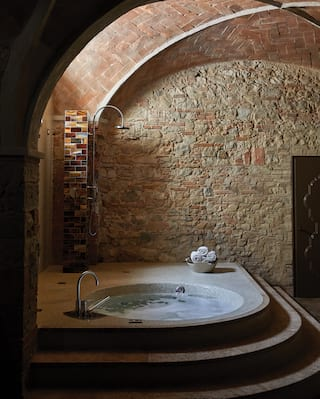 Circular hot tub in a rustic, underground, stone-walled spa