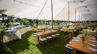 Wooden banquet tables set for a wedding under a large white tent canopy