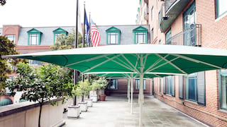 Green parasols over a patio in front of a red-bricked building lined by flag poles