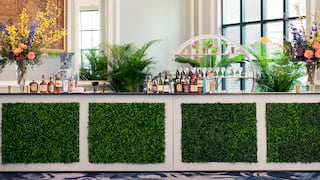 Bar counter with faux foliage square insets and topped with liquor bottles