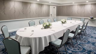 Oval linen-topped banquet table with powder blue event chairs set for a meeting