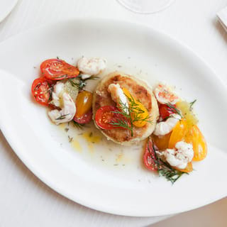 Birds-eye-view of a pan-seared scallop surrounded by crab meat and tomatoes