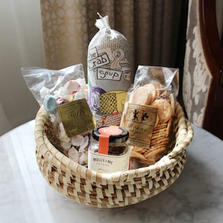 Close-up of a gift basket with cookies, sweets and jelly on a marble-topped table