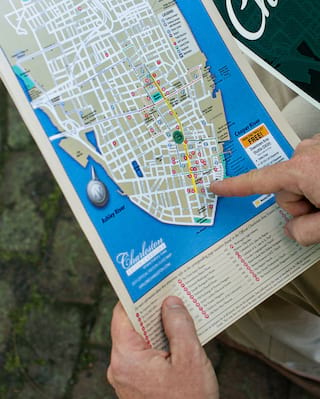 Close-up of a finger pointing to a spot on a map of Charleston