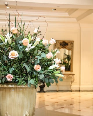 Large bouquet of blush pink roses and white lillies on a Grecian plinth