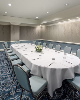 Oval linen-coated banquet table set for a meeting in a spacious room