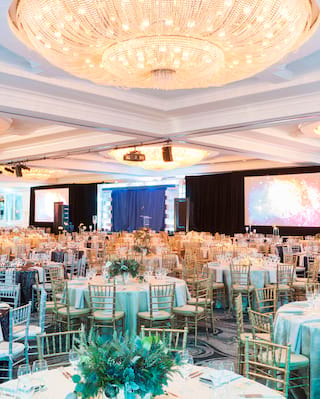 Vast ballroom with grand dome chandeliers and circular banquet tables