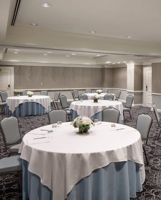 Circular banquet tables with white floral centrepieces in a spacious, elegant room