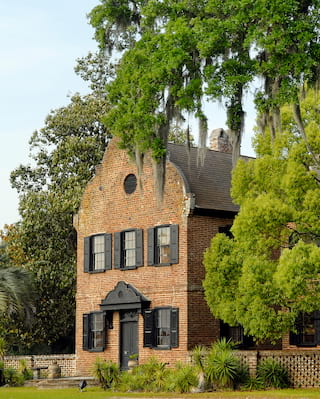 Medieval-style red-brick mansion surrounded by trees