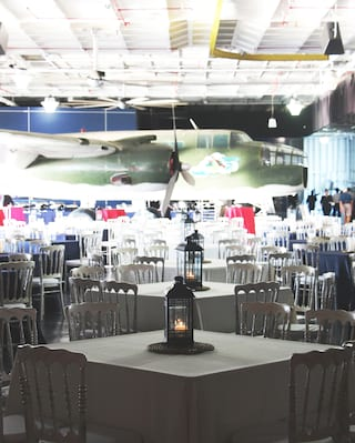 Rows of square tables with candle lantern centerpieces facing an air-force plane