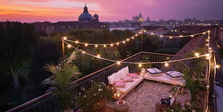 Guests party on a beautiful Venetian rooftop at sunset
