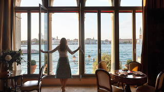 Lady looking through the window of a hotel suite overlooking the Venice lagoon