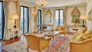 Hotel suite lounge with ornate gold mirrors, gold velvet furnishings and candelabra light
