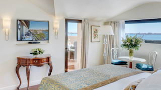 Bright and airy hotel room with a soft pillowy bed, barrel-vaulted ceiling and sea views