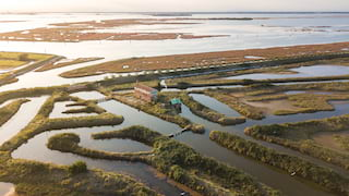 Aerial view of a rustic farm building on an island of sandbanks in the Venetian lagoon