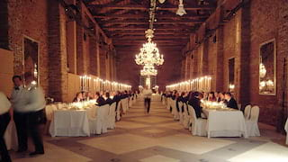 Interior of a brick granary with a grand chandelier and banquet tables lining the sides