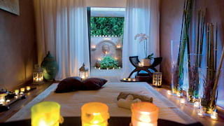 Candlelit spa treatment room with open patio doors leading to a courtyard beyond