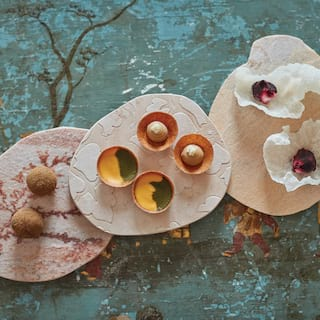 Three platter dishes topped with modern art-inspired canapés