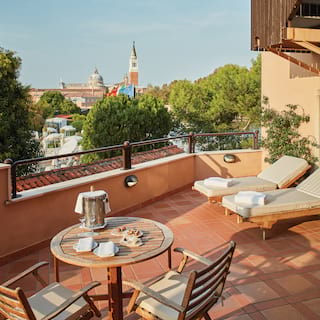 Terracotta-tiled hotel terrace with two sunbeds and views of St Mark's Square