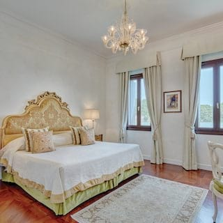 Stylish hotel room with a baroque-style pillowy king-bed and candelabra ceiling light