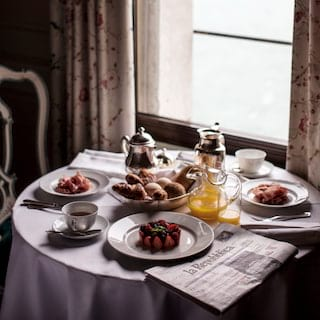 In-room dining table laden with breakfast dishes and a daily newspaper