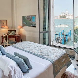 Light and airy hotel suite with open windows and views across the Venetian lagoon