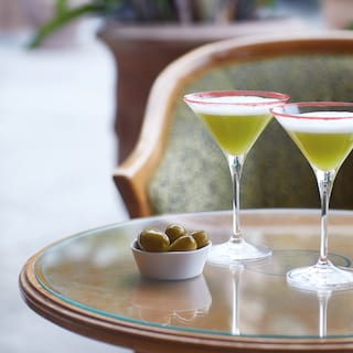 Two joker cocktails served with olives on a polished circular wooden table