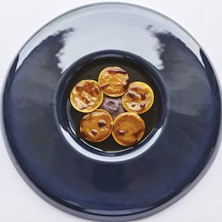Birds-eye-view of a black glazed circular bowl containing ravioli parcels