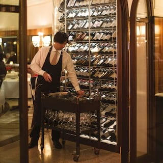 Sommelier selecting bottles from a lamplit wine display