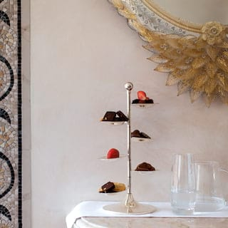 Six-tiered cake stand laden with sweet treats on a room service tray