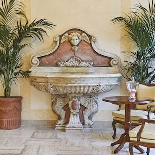 Ornate baroque indoor fountain surrounded by potted palm plants