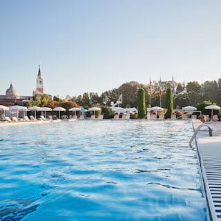 View over gentle waves of an outdoor hotel pool with St Mark's Square in the distance