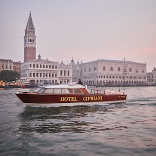 Venetian water taxi emblazoned with 'Hotel Cipriani' sailing by St Mark's square