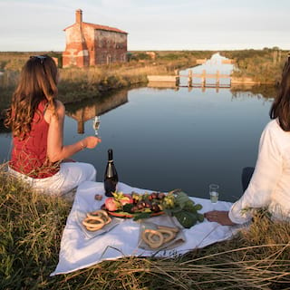 Two guests enjoying a champagne picnic on the shore of a canal at sunset