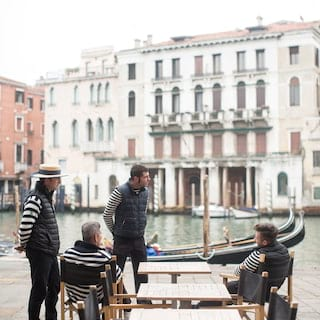 Four gondola boatmen in striped attire relaxing beside their gondolas
