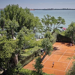 Aerial view of a clay tennis court surrounded by lush garden foliage