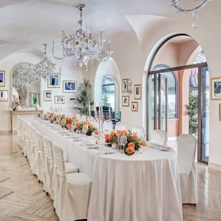 Banquet table set for a wedding in a light barrel-vaulted room with chandeliers