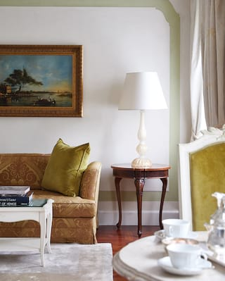 Gold-patterned sofa with a green cushion beside a mahogany table with a white lamp