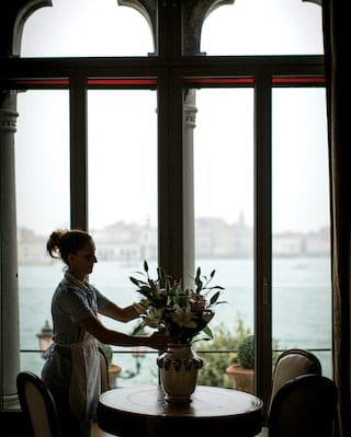 Housekeeper tending to a flower vase in a luxury suite