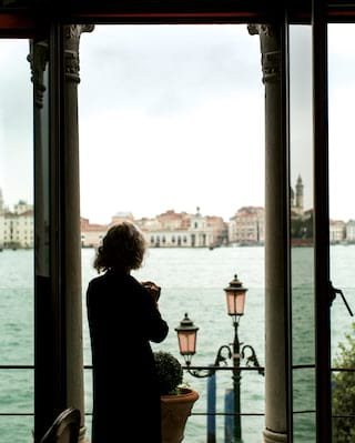 Lady gazing from a hotel suite balcony across the Venetian lagoon