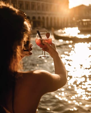 Lady photographing a sangria cocktail at sunset
