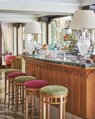 Stylish bar with a green marble counter top with liquor on glass shelves behind