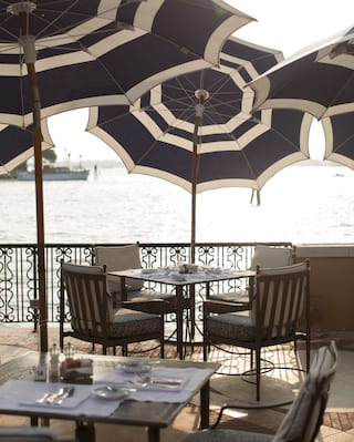 Square outdoor café table with navy striped parasols overlooking Venice