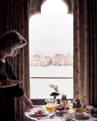 In-room dining table laden with breakfast dishes overlooking St Mark's Square