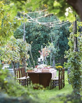 View through garden foliage of an outdoor banquet table under an ivy pergola