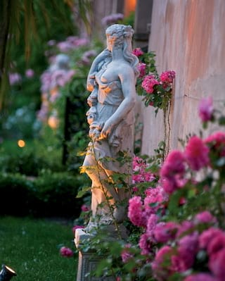 Close-up of a Venus statuette surrounded by pink flowers in a lamplit garden